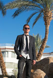 Man in sunglasses and in a jacket at the palm tree Royalty Free Stock Images