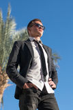 Man in sunglasses and in a jacket at the palm tree Stock Photography