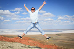 Man in sunglasses jumping over blue sky Stock Images