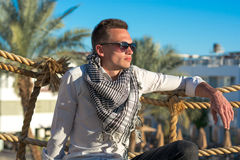 Man in the sunglasses and in the keffiyeh sits near a palm trees Stock Image