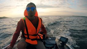A man in sunglasses and a life vest is drifting in a boat