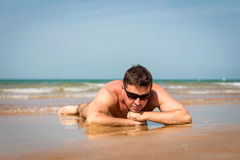 Man in sunglasses lying on a beach on sea background. Man in sunglasses lying on the beach on sea background Stock Photo