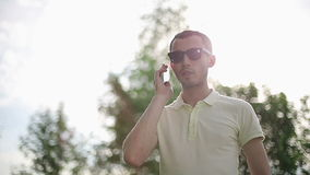 Man in sunglasses outdoors talking on the phone at sunset slow motion stock video