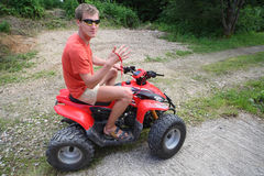 A man in sunglasses on a quad bike ride. On impassability royalty free stock images
