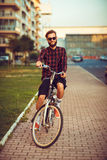 Man in sunglasses riding a bike on city street Stock Images