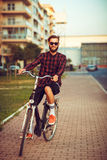 Man in sunglasses riding a bike on city street Royalty Free Stock Photos