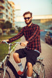 Man in sunglasses riding a bike on city street Stock Photo