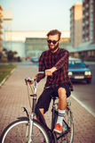 Man in sunglasses riding a bike on city street Stock Photography