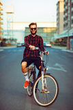 Man in sunglasses riding a bike on city street Royalty Free Stock Photo