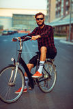 Man in sunglasses riding a bike on city street Stock Image