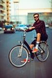 Man in sunglasses riding a bike on city street Stock Photos