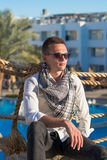 Man in the sunglasses, in the shirt and in the keffiyeh sits nea Royalty Free Stock Images