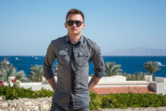 Man in sunglasses and a shirt near the sea Stock Image