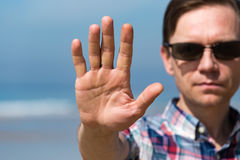 Man in Sunglasses Showing Stop Sign with his Hand Stock Image