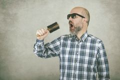 Man with sunglasses singing a hair brush stock photography