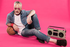 Man in sunglasses sitting near tape recorder and basketball ball Stock Photo