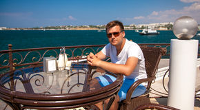 Man in sunglasses sitting on terrace in cafe Stock Photography