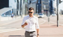 Man in sunglasses with smartphone walking at city Royalty Free Stock Photo