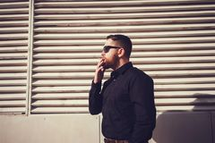 Man in sunglasses smoking a cigarette. Bearded man in sunglasses smoking a cigarette on a wooden background Royalty Free Stock Photo