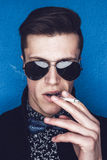 Man in sunglasses smoking a cigarette Royalty Free Stock Images