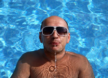 Man in sunglasses spits a stream of water in pool stock image