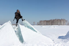 Man in sunglasses standing on cracked ice on the river. Man in sunglasses standing on cracked ice, Ob River, Russia royalty free stock photos
