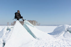 Man in sunglasses standing on cracked ice on the river. Man in sunglasses standing on cracked ice, Ob River, Russia stock image