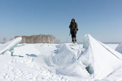 Man in sunglasses standing on cracked ice on the river. Man in sunglasses standing on cracked ice, Ob River, Russia stock images