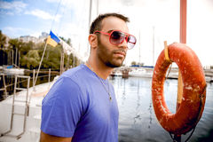 Man in sunglasses standing at seaport against yachts and lifebuoy Stock Photo