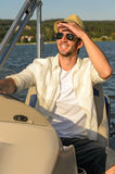 Young man navigating powerboat sunny. Man in sunglasses and straw hat navigating boat sunny day Royalty Free Stock Photography