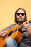 Man in sunglasses strumming a guitar Royalty Free Stock Photography