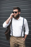 Man in sunglasses and suspenders using smartphone and looking away. Stylish man in sunglasses and suspenders using smartphone and looking away Royalty Free Stock Images
