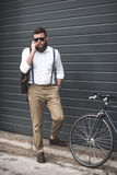 Man in sunglasses and suspenders using smartphone and standing near bike. Stylish man in sunglasses and suspenders using smartphone and standing near bike Stock Image