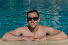 Man in sunglasses swimming in an outdoor pool. Young handsome man in sunglasses swimming in an outdoor pool during holiday on sunny summer day Stock Photos