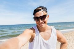 Man in sunglasses taking selfie on summer beach. Summer holidays and people concept - happy smiling young man in sunglasses and hat taking selfie on beach Stock Image