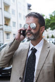Man with sunglasses talking on the phone Royalty Free Stock Image