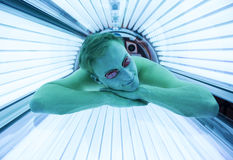 Man with sunglasses on tanning bed in solarium Stock Images