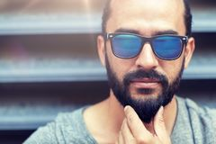 Man in sunglasses touching beard on city street. Lifestyle, emotion, expression and people concept - man in sunglasses touching beard on city street Stock Images