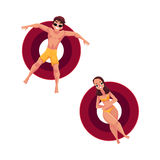 Man in sunglasses and woman wearing bikini on inflatable rings Stock Photos