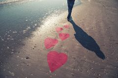 Man on the sunny beach with illustrated heart symbols royalty free stock images