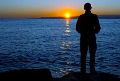Man on sunrise. Man on sea coast in sunrise Royalty Free Stock Photography