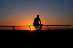 Man at sunset. Silouette of man sitting on the rails(fence) at synset Royalty Free Stock Photo