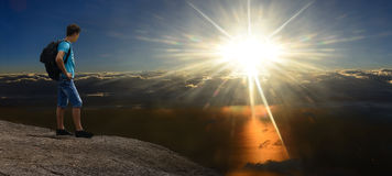 Man on sunshining rock above stormy clouds. Panorama