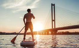 Man on SUP board. Man on stand up paddle board. Having fun on SUP board during sunset. Active lifestyle Royalty Free Stock Photos