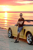 Man with super car on back of sunset Stock Image