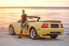 Man with super car on back of sunset Royalty Free Stock Photography