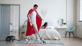 Man in superhero cape vacuuming carpet at home while lady reading book in bed. Man in superhero cape and mask is vacuuming carpet at home while young lady is stock video footage