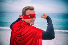 Man in superhero costume flexing muscles at sea shore Royalty Free Stock Photography