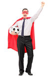 Man in superhero costume holding a football. Isolated on white background Stock Photos