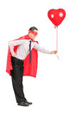 Man in superhero costume holding a red balloon Royalty Free Stock Image